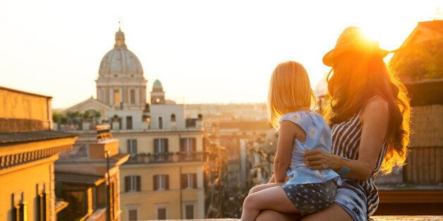 Mother and baby girl sitting on street overlooking rooftops of rome on sunset looking into