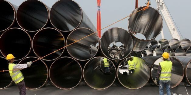 Workers unload newly arrived pipes for the construction of the future Trans-Adriatic Pipeline in Spitalle,...