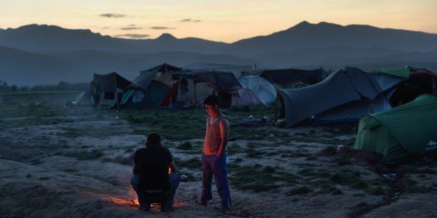 Two persons stand by a fire at a makeshift camp set by migrants and refugees at the Greek-Macedonian...