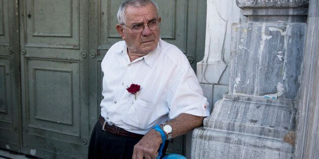 A pensioner stands outside the main gate of the national bank of Greece as he waits to withdraw a maximum...