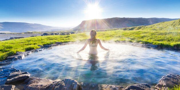woman bathing in natural hot spring, rays of light glistening, mountains in