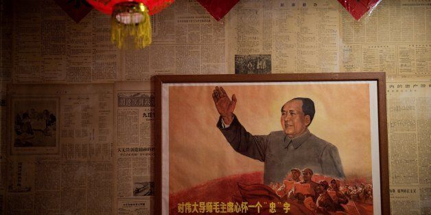 A poster showing the late Chinese chairman Mao Zedong hangs on a wall inside a restaurant in Beijing...
