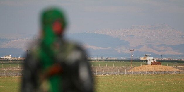 A Kurdish member of the Self-Defense Forces stands near the Syrian-Turkish border in the Syrian city...