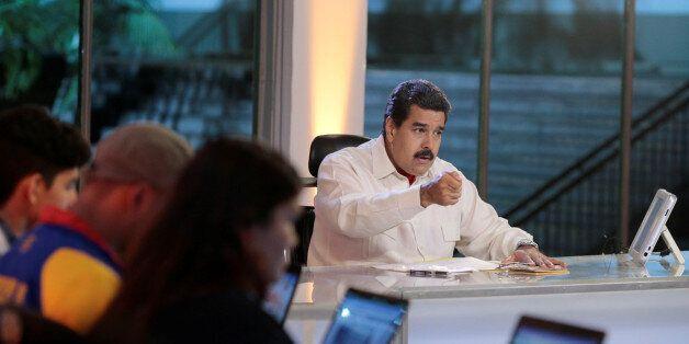 Venezuela's President Nicolas Maduro (C) speaks during his weekly