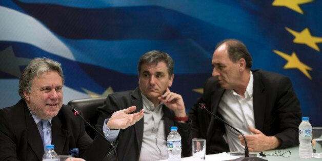 Greek Labour Minister George Katrougalos, left, speaks next to Greek Finance Minister Euclid Tsakalotos,...