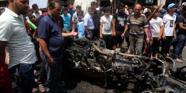 Citizens inspect the scene after a car bomb explosion at a crowded outdoor market in the Iraqi capital's...