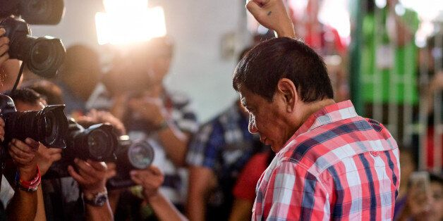 Rodrigo Duterte, Mayor of Davao and presidential candidate, gestures to members of the media at a polling...