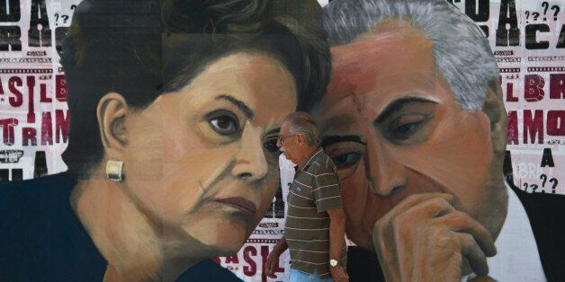 A man walks past a mural depicting Brazilian President Dilma Rousseff (L) and Vice-President Michel Temer...