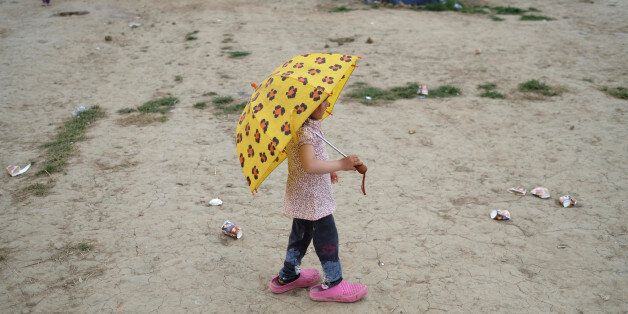 A girl holds an umbrella at a makeshift camp for migrants and refugees at the Greek-Macedonian border...