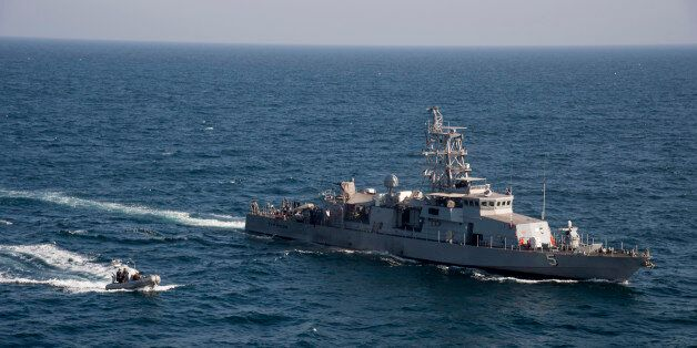 In this photo released by the U.S. Navy on Feb. 21, 2014, a rigid hull inflatable boat transits alongside...