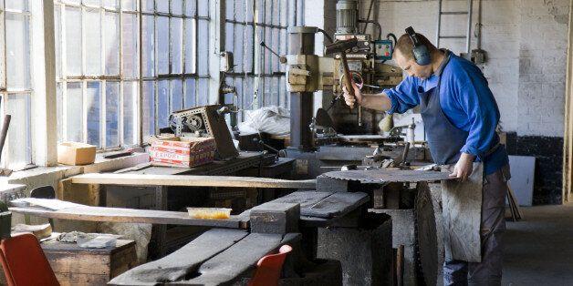 Man checking straightness of saw blade with metal guage. Straightening saw blade by process of