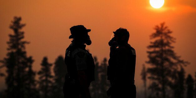 Two RCMP police officers wear gas masks in the smoke from the wildfires near Fort McMurray, Alberta,...