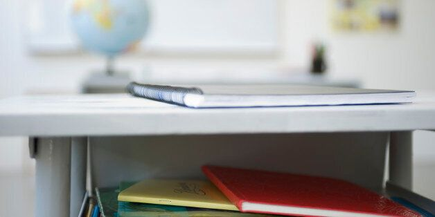 School desk containing stack of books,
