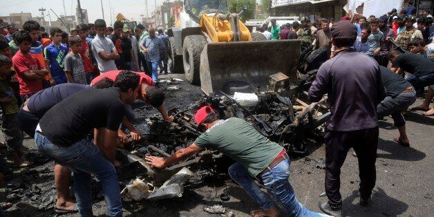Civilians help a municipality bulldozer cleans up while citizens inspect the scene after a car bomb explosion...