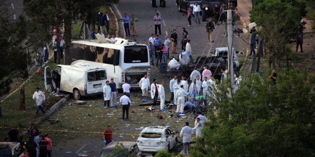 Security officers and medics work at the explosion site after a car bomb struck a bus in Diyarbakir,...
