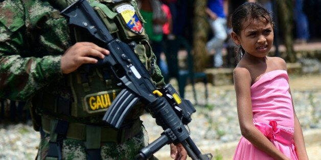 A Colombian Senu native girl stands next to soldiers during a ceremony at the new indigenous village...