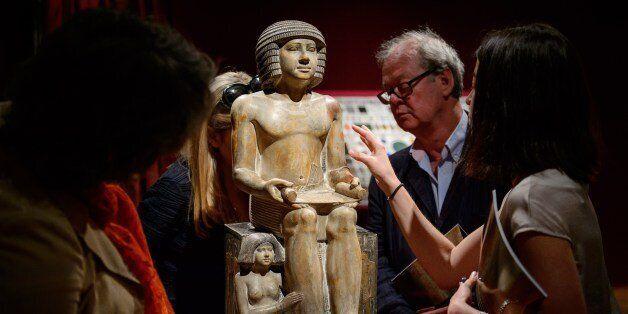 Members of the public and gallery staff examine The Northampton Sekhemka, an Egyptian painted limestone...