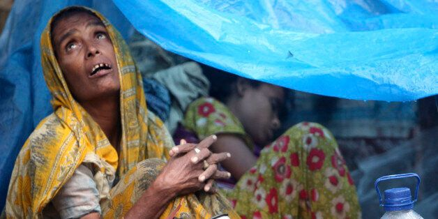 FILE - In this July, 28, 2009 file photo, a Bangladeshi woman looks skyward from inside her temporary...