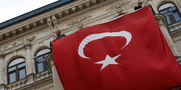A Turkey national flag is hung on a balcony in Istiklal Street near the scene of Saturday's bomb explosion,...