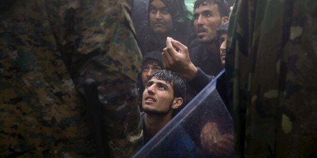 Migrants and refugees beg Macedonian policemen to allow passage to cross the border from Greece into...
