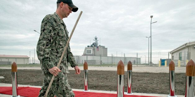 A US serviceman, backdropped by the radar building of a missile defense base, carries a mop in Deveselu,...