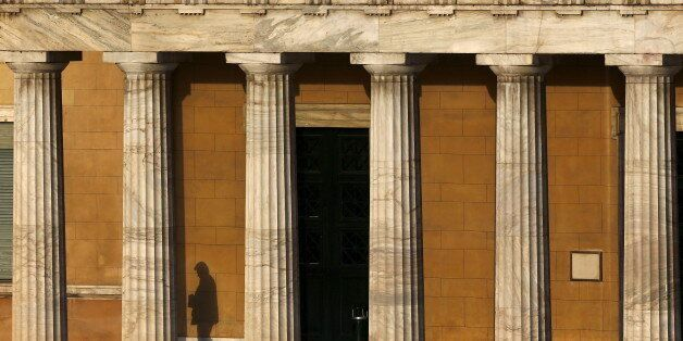 A man's shadow is seen as he leaves from the western entrance of the Greek parliament in Athens May 6,...