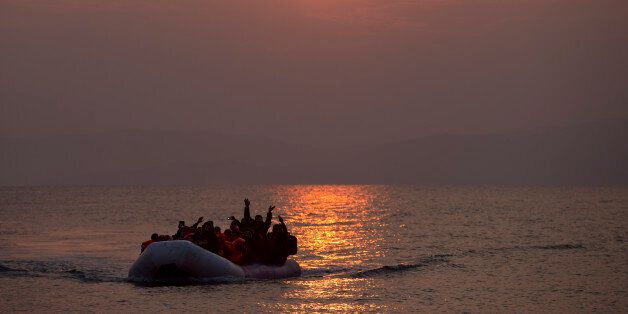The sun rises as migrants and refugees on a dingy arrive at the shore of the northeastern Greek island...