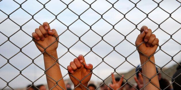 Syrian refugee children chant slogans behind a fence at the Nizip refugee camp in Gaziantep province,...
