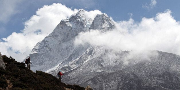 In this March 5, 2016 photo, trekkers hike at the base of Mount Ama Dablam (6856 meters) in the Khumbu...