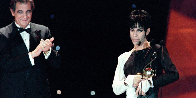 This photo taken on May 4, 1994 shows musician Prince (R) acknowledging applause after receiving from Italian tenor Placido Domingo (L) the 'Outstanding Contribution to the Pop Industry' award during the World Music Awards ceremony in Monaco.Pop icon Prince -- whose pioneering brand of danceable funk made him one of music's most influential figures -- died on April 21, 2016 at his compound in Minnesota. He was 57. The announcement came just a week after the Grammy and Oscar winner was taken to hospital with a bad bout of influenza, although he made light of his health problems after the scare. / AFP / Patrick HERTZOG        (Photo credit should read PATRICK HERTZOG/AFP/Getty Images)