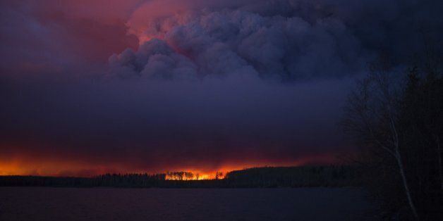 A massive wildfire, which caused a mandatory evacuation, rages south of Fort McMurray near Anzac, Alberta,...