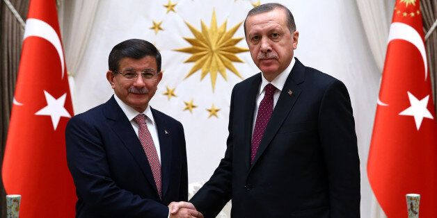 Turkey's Prime Minister Ahmet Davutoglu left, and President Recep Tayyip Erdogan shake hands before a...