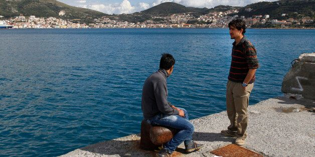 Migrants sit near their temporary housing at the port of the eastern Greek Island of Samos, in the Aegean...