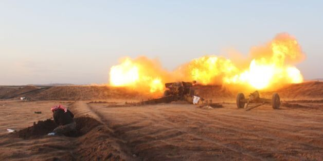 A rebel fighter from the Jaish al-Fatah (or Army of Conquest) brigades fires artillery during clashes...