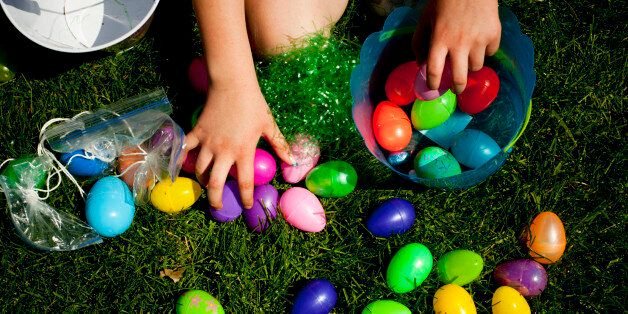 A child reaches for Easter eggs in the grass on a farm in