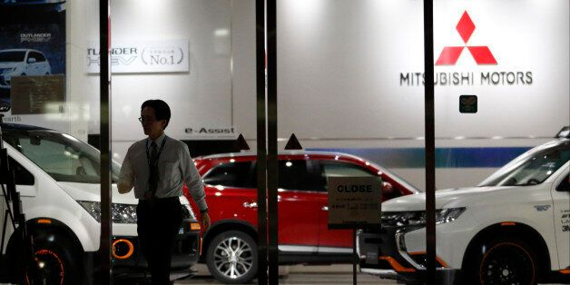 TOKYO, JAPAN - APRIL 20: An employee walks past a Mitsubishi Motors vehicles displayed at the company's...
