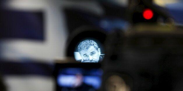 Greek Finance Minister Euclid Tsakalotos is seen through a camera viewfinder during a news conference...