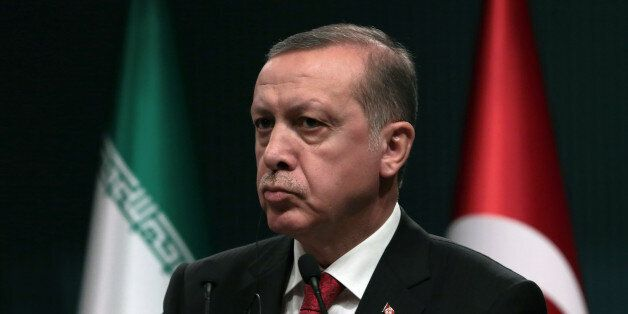 Turkey's President Recep Tayyip Erdogan listens to Iran's President Hassan Rouhani during a joint news...