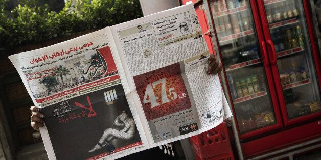A woman reads a copy of Egyptian newspaper 'Al-Tahrir' with the headline 'No to Dictatorship' on December...
