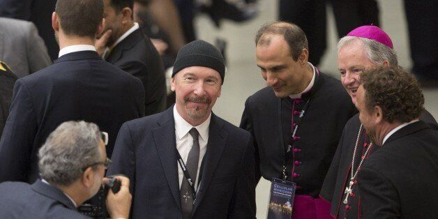 VATICAN CITY, VATICAN - APRIL 29: U2 rock band's guitarist The Edge (C) pose for a photo with some bishops...