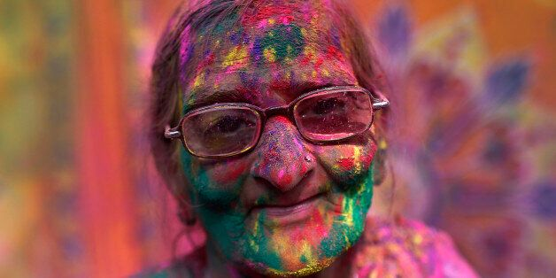 A widow daubed in colours takes part in Holi celebrations organised by non-governmental organisation...