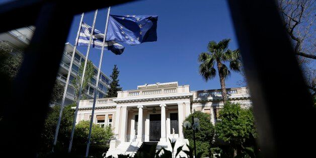 The Greek and the European Union flags are wave outside Maximos Mansion, office of the Prime Minister...