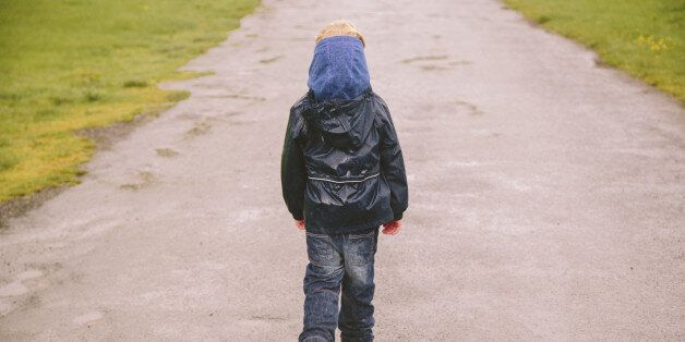 Little boy walking down a country road in the Lake District on a rainy