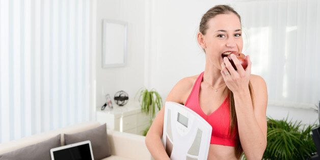 cheerful young woman holding scales and eating fruit weight loss