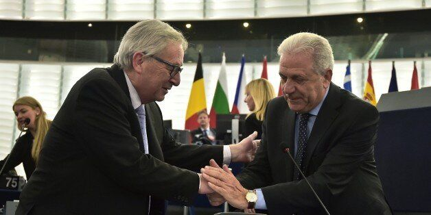 European Commission President Jean-Claude Juncker (L) shakes hands with EU Commissioner for Migration...