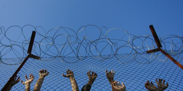 Immigrants lean on fences during unrest inside Pagani detention centre, in the eastern Aegean island...