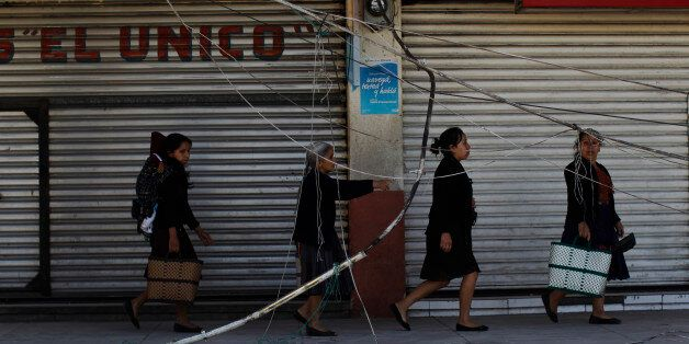 Women walk past a damaged wall of the central market in San Pedro, in the northwest region of San Marcos,...