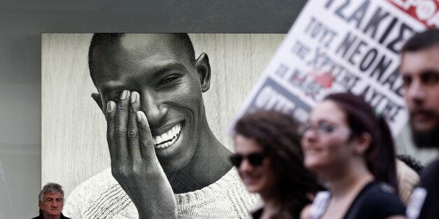Protesters march past an advertising poster during an anti-racism rally in Athens, March 22, 2014. Thousands...