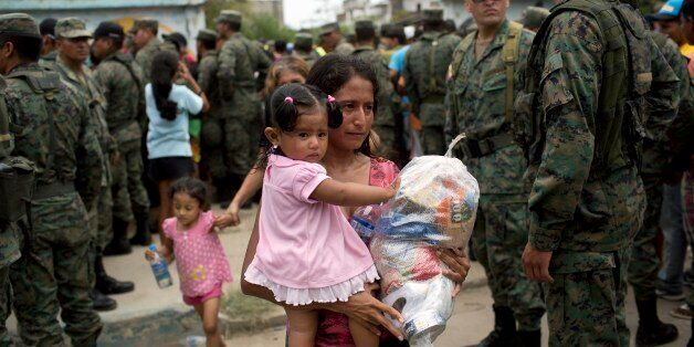 A woman and child walk away with free food and water from the government, after waiting for hours, days...