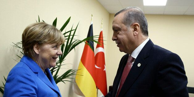 Turkey's President Recep Tayyip Erdogan, right, and German Chancellor Angela Merkel shake hands during...